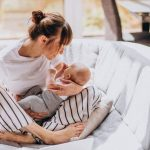 mother with newborn on couch breastfeeding