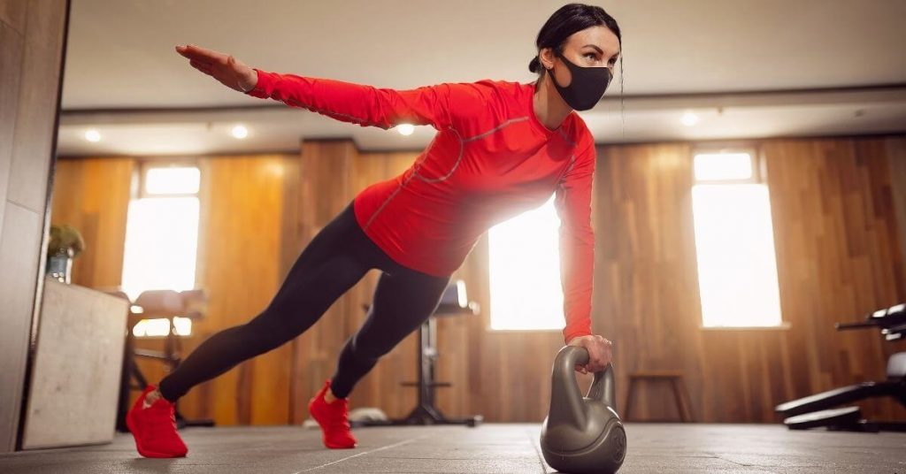 woman exercising while wearing a medical mask